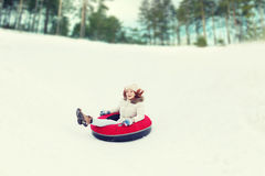 Adolescente feliz que resbala abajo en el tubo de la nieve Imágenes de archivo libres de regalías