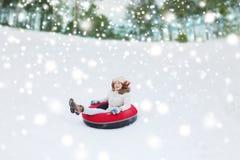 Adolescente feliz que resbala abajo en el tubo de la nieve Fotos de archivo libres de regalías