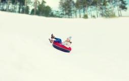 Adolescente feliz que resbala abajo en el tubo de la nieve Imagen de archivo