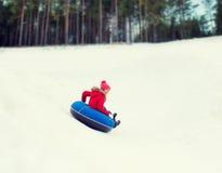 Adolescente feliz que resbala abajo en el tubo de la nieve Imagen de archivo libre de regalías