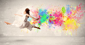 Adolescente feliz que salta con la salpicadura colorida de la tinta en backg urbano Foto de archivo