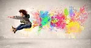 Adolescente feliz que salta con la salpicadura colorida de la tinta en backg urbano Imagenes de archivo