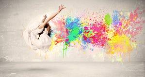 Adolescente feliz que salta con la salpicadura colorida de la tinta en backg urbano Imágenes de archivo libres de regalías