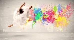 Adolescente feliz que salta con la salpicadura colorida de la tinta en backg urbano Foto de archivo libre de regalías