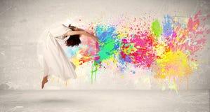 Adolescente feliz que salta con la salpicadura colorida de la tinta en backg urbano Imagen de archivo
