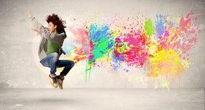 Adolescente feliz que salta con la salpicadura colorida de la tinta en backg urbano Fotografía de archivo