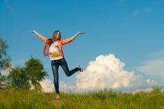 Adolescente feliz que salta en el fondo del verano al aire libre Foto de archivo