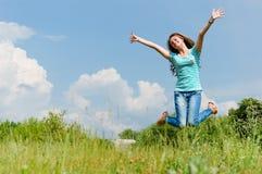 Adolescente feliz que salta en el fondo del verano al aire libre Fotografía de archivo