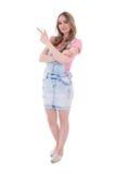 Adolescente feliz que señala en algo aislado en blanco Imagenes de archivo