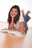 Adolescente feliz que se acuesta con el libro Fotos de archivo libres de regalías