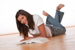 Adolescente feliz que se acuesta con el libro Foto de archivo