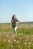 Adolescente feliz que se ejecuta en el prado Imagenes de archivo