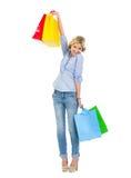 Adolescente feliz que se levanta encima de bolsos de compras Fotos de archivo libres de regalías