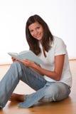 Adolescente feliz que se sienta con el libro Foto de archivo