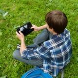 Adolescente feliz que se sienta en hierba en parque Foto de archivo libre de regalías