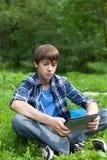 Adolescente feliz que se sienta en hierba en parque Fotos de archivo