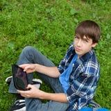 Adolescente feliz que se sienta en hierba en parque Imagen de archivo libre de regalías