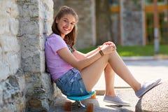 Adolescente feliz que se sienta en longboard en la calle Imagen de archivo libre de regalías