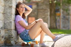 Adolescente feliz que se sienta en longboard en la calle Fotografía de archivo