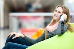 Adolescente feliz que se sienta en silla del beanbag en inte contemporáneo Fotos de archivo libres de regalías