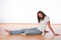 Adolescente feliz que se sienta en suelo de madera Fotos de archivo