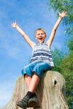 Adolescente feliz que se sienta en un tocón Fotografía de archivo libre de regalías