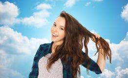 Adolescente feliz que sostiene el filamento de su pelo Imagen de archivo libre de regalías