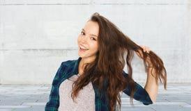 Adolescente feliz que sostiene el filamento de su pelo Fotografía de archivo