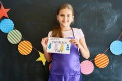 Adolescente feliz que sostiene la tarjeta de felicitación para el día de padres Imagen de archivo libre de regalías