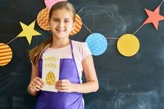 Adolescente feliz que sostiene la tarjeta de felicitación de Pascua Fotografía de archivo