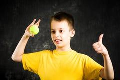 Adolescente feliz que sostiene una pelota de tenis Foto de archivo libre de regalías