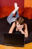 Adolescente feliz que tem o divertimento com caderno em casa Fotos de Stock