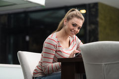 Adolescente feliz que usa a almofada de toque no café Imagem de Stock