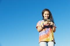 Adolescente feliz que usa el móvil en parque Imagen de archivo