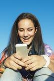 Adolescente feliz que usa el móvil en parque Fotografía de archivo
