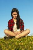 Adolescente feliz que usa el móvil en parque Imagenes de archivo