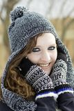 Adolescente feliz que veste fora o chapéu e mittnes preto e branco do inverno imagens de stock