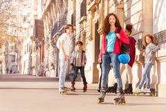 Adolescente feliz rollerblading con los amigos Imagen de archivo