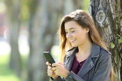 Adolescente feliz usando un teléfono elegante al aire libre Foto de archivo