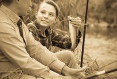 Adolescente feliz y padre del muchacho que pescan junto Imagenes de archivo