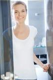 Adolescente feliz y sonriente en un cuarto de baño Foto de archivo