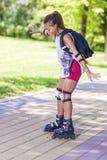 Adolescente femenino afroamericano activo y juguetón feliz que se divierte en pcteres de ruedas en parque Fotos de archivo
