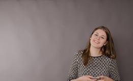 Adolescente femenino alegre con un teléfono móvil Imágenes de archivo libres de regalías
