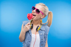 Adolescente femenino alegre que sostiene la piruleta Imagenes de archivo