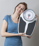 Adolescente femenino alegre que sostiene su escala con amor y la satisfacción Foto de archivo libre de regalías