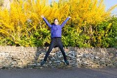 Adolescente femenino asiático feliz que salta con alegría delante del amarillo fotos de archivo