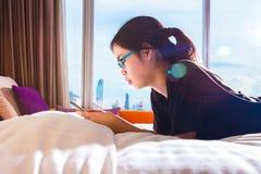 Adolescente femenino asiático que usa su teléfono elegante en la cama, sunl de la mañana Fotografía de archivo