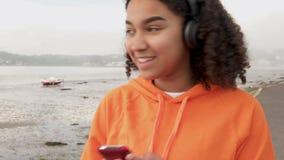 Adolescente femenino Biracial que escucha la música en los auriculares inalámbricos usando su teléfono celular elegante almacen de metraje de vídeo