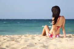 Adolescente femenino bonito que mira el mar en la playa Imagen de archivo libre de regalías