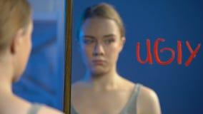 Adolescente femenino bonito que mira la superficie escrita fea del espejo de la palabra, edad de la pubertad almacen de metraje de vídeo